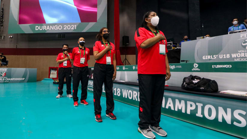 Torrealva and her coaching staff line up during the Peruvian national anthem