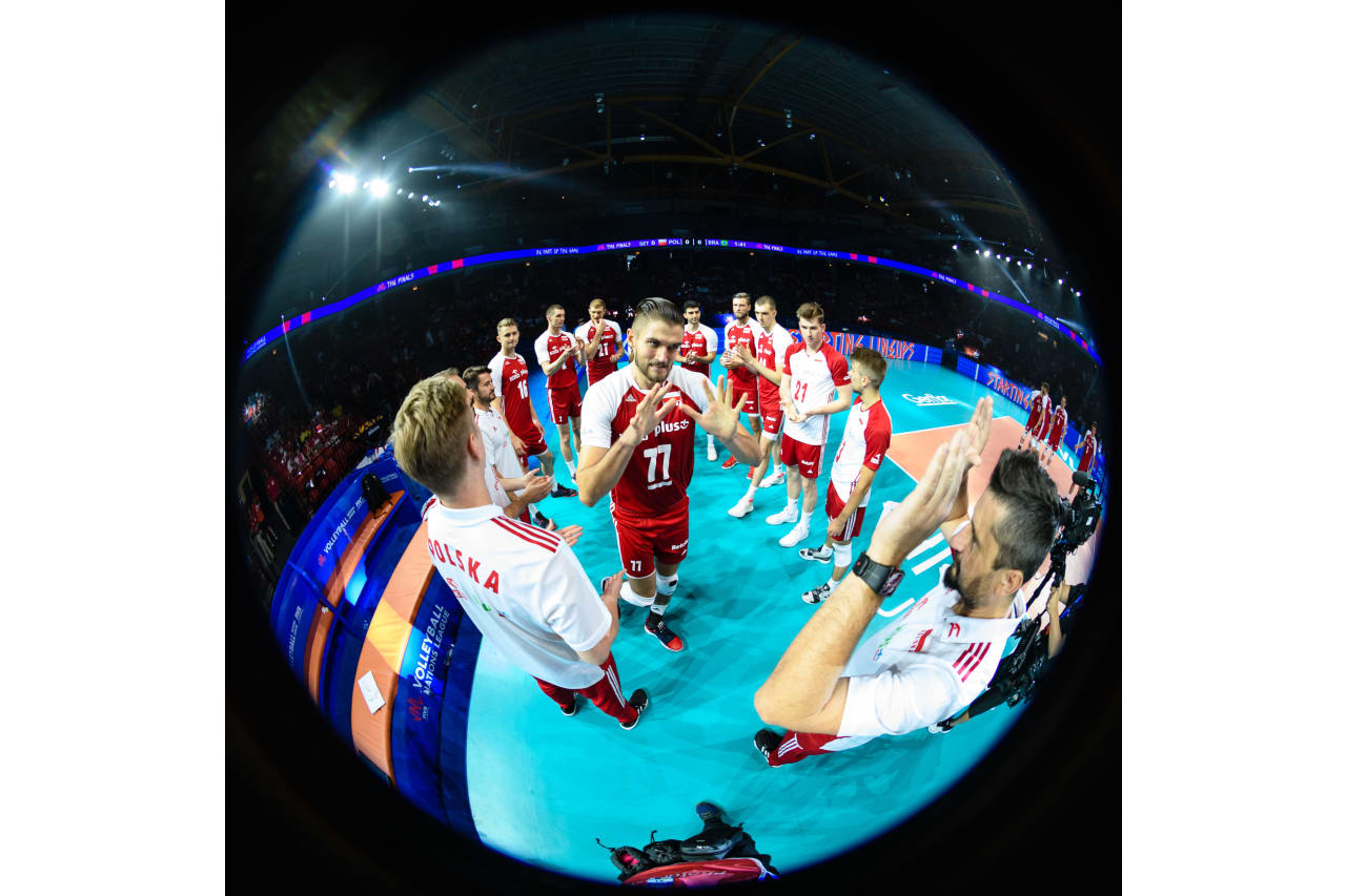 Poland's Karol Klos high fives a coaching staff member before he enters the court