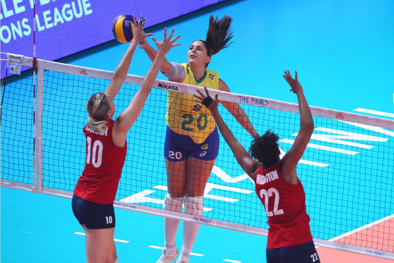 Brazil's Ana Beatriz Correa spikes against the American block