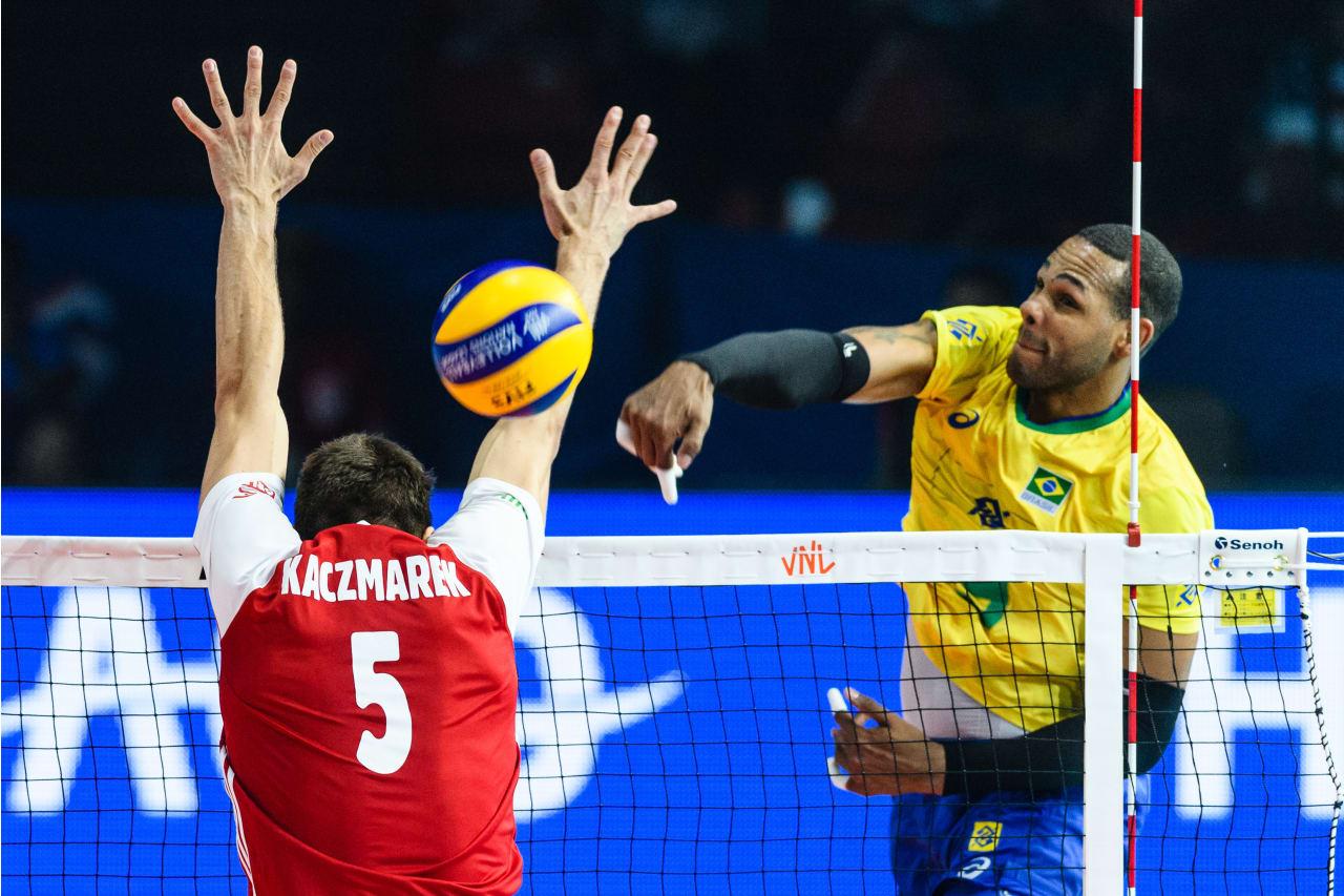 Brazil's Yoandy Leal spikes past the Polish block