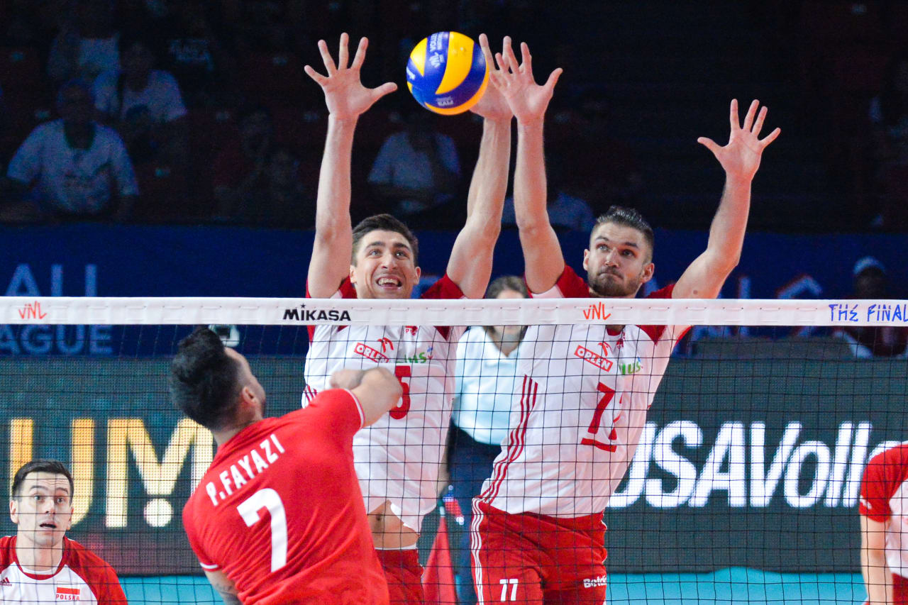 Poland's Lukasz Kaczmarek (5) and Karol Klos (77) attempt to block Iran's spike
