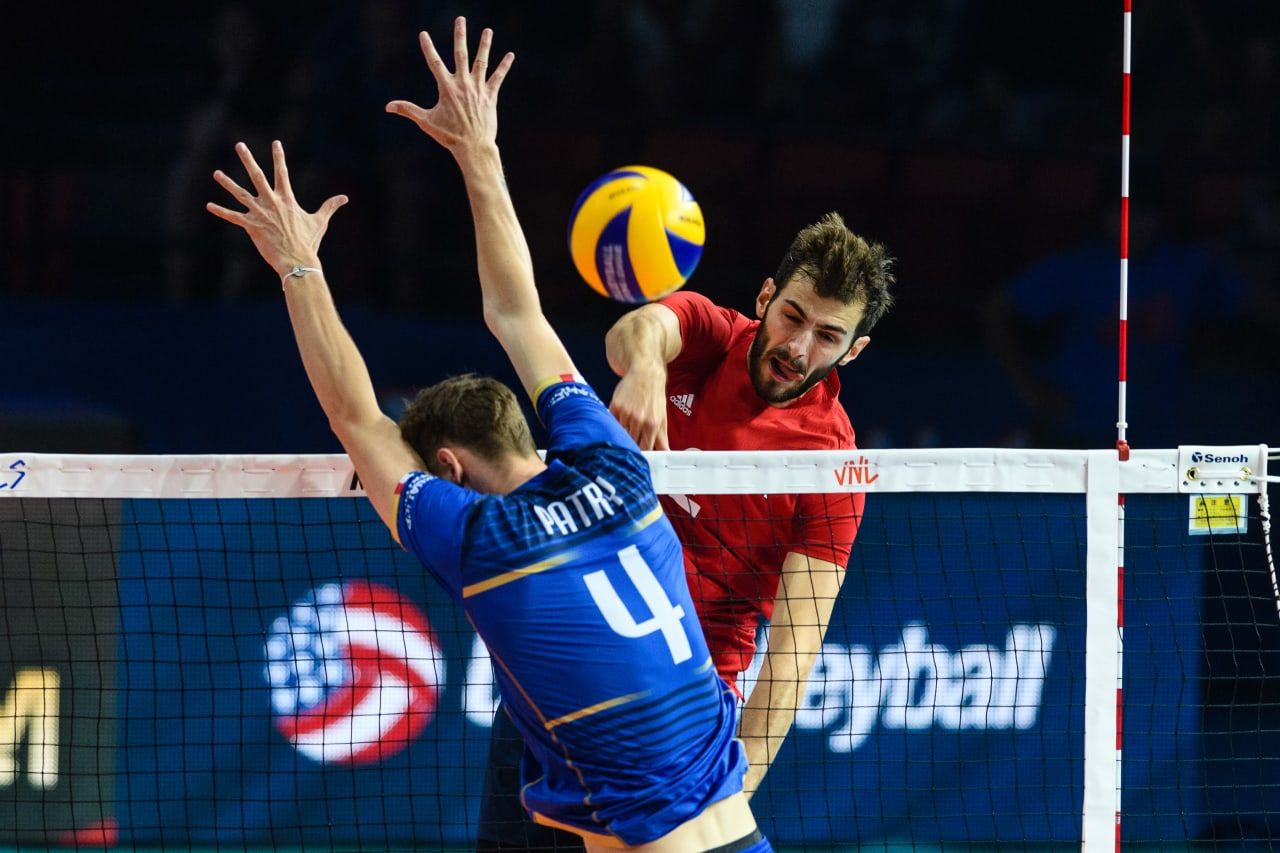 USA's Aaron Russell spikes the ball past the French block